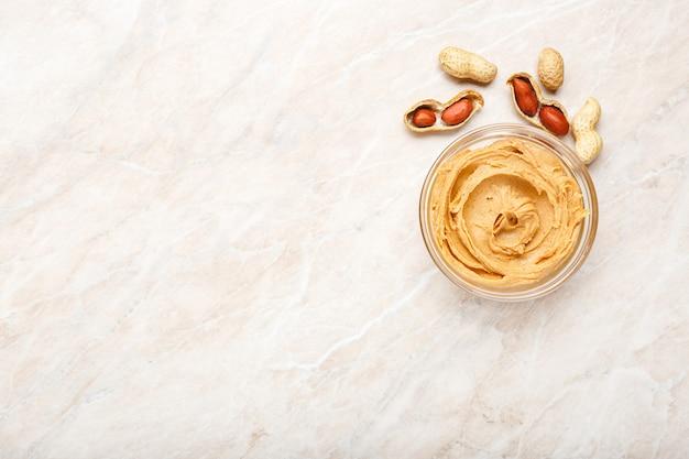 Manteiga de amendoim em uma placa de vidro com amendoim com casca e amendoim descascado. pasta cremosa de amendoim plana leigos com lugar para texto em fundo de mármore branco para cozinhar o café da manhã. conceito de comida vegana.