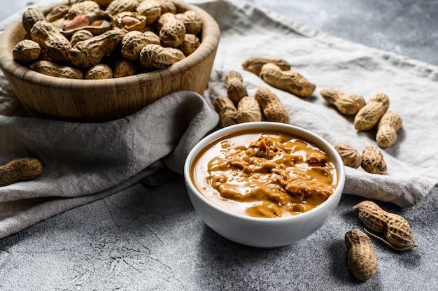 Manteiga de amendoim em uma tigela, amendoim cru. comida vegetariana saudável. .