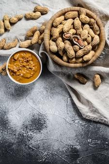 Manteiga de amendoim em uma tigela, amendoim cru, comida vegetariana, vista superior, espaço para texto