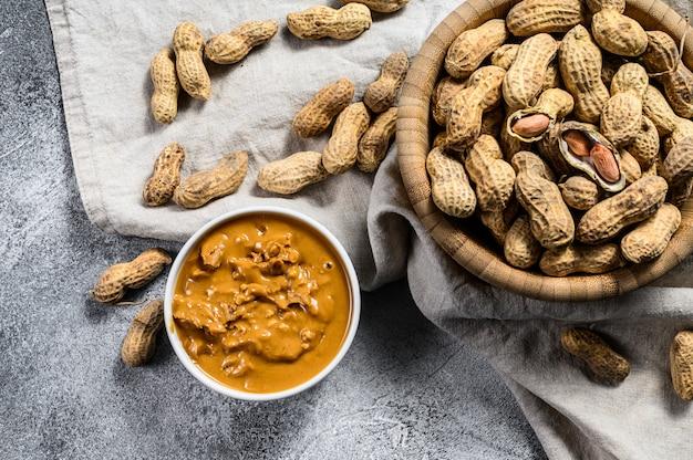 Manteiga de amendoim em uma tigela, amendoins crus, comida vegetariana saudável, vista superior.