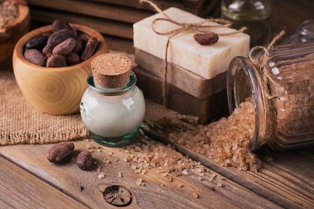 Manteiga de cacau cosmética natural, sal marinho e sabonete artesanal natural com grãos de cacau em fundo de madeira rústico. cuidados com a pele saudável. conceito de spa.