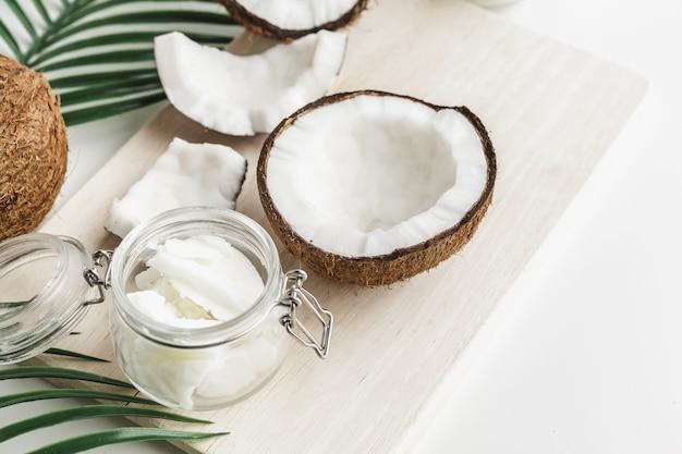Manteiga de coco saudável orgânica e pedaços de coco fresco na placa de madeira
