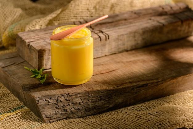 Manteiga de ghee em frasco de vidro com espátula de madeira sobre madeira