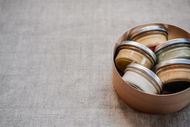 Manteiga de nozes e sementes em potes de vidro com fundo de tecido natural com copyspace caseiro cru orgânico