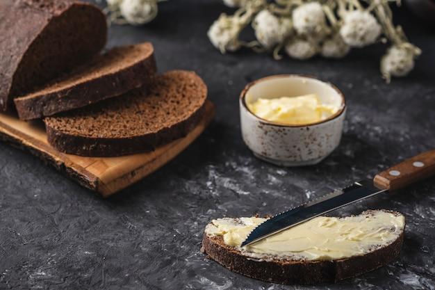 Manteiga de pão fatiado na superfície escura