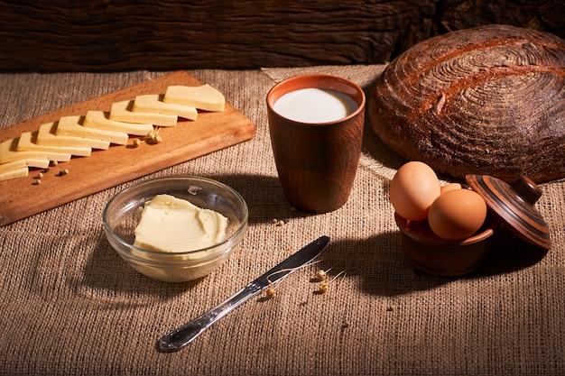Manteiga e chees e leite para o café da manhã, sobre o fundo de madeira rústico com espaço da cópia.