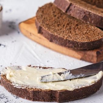 Manteiga e faca de pão fatiado na superfície da luz. fechar-se