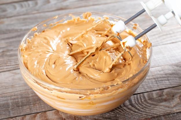 Manteiga e leite condensado fervido em uma tigela de vidro com uma batedeira. fazendo creme para bolo