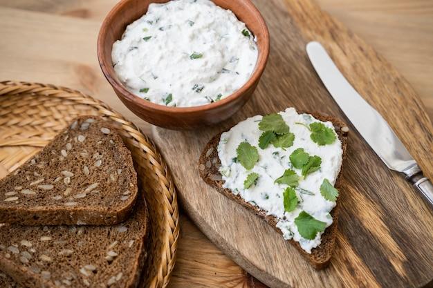 Manteiga e pão no café da manhã, com salsa sobre fundo de madeira rústico close-up.
