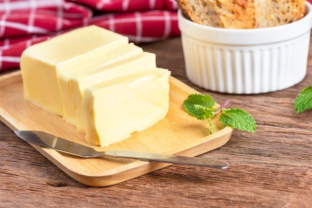 Manteiga fresca cortada com a faca na placa e no pão de madeira.