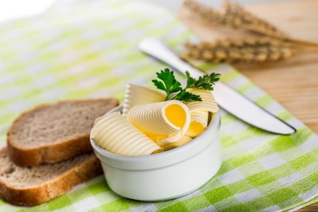 Manteiga fresca fatiada com folhas de salsa em uma tigela branca em um guardanapo xadrez