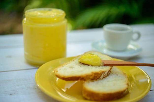 Manteiga ghee com pão fatiado em prato amarelo na mesa do café da manhã com pote de vidro de manteiga e xícara