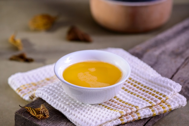 Manteiga ghee da índia em um recipiente de talheres branco na mesa de madeira.