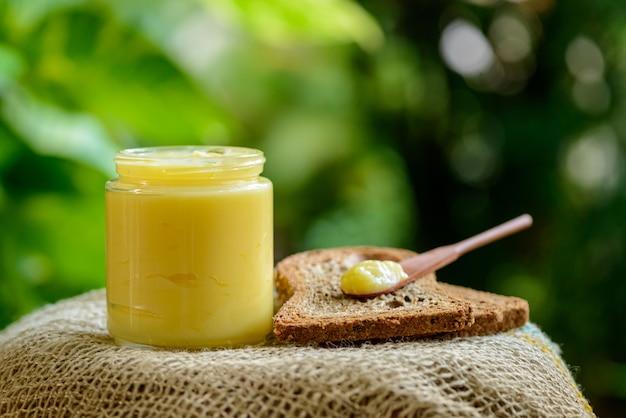 Manteiga ghee em frasco de vidro com espátula de madeira sobre uma fatia de pão integral no fundo desfocado