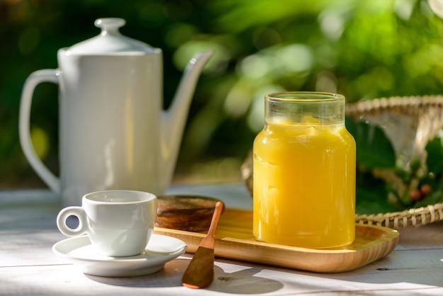 Manteiga ghee em frasco de vidro na mesa do café da manhã com bule e xícara brancos