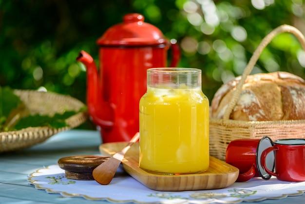 Manteiga ghee em frasco de vidro na mesa do café da manhã com bule e xícaras vermelhas.