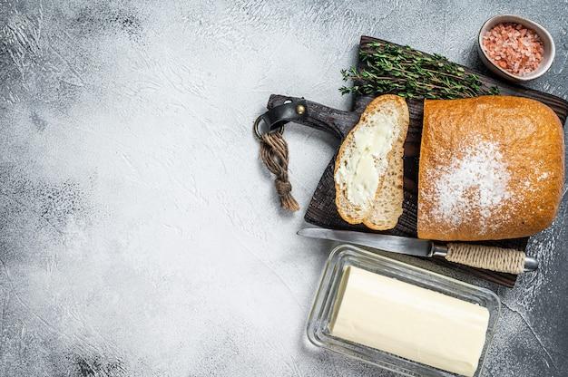 Manteiga o bloco e as torradas de pão fatiadas em uma placa de madeira com ervas. fundo branco. vista do topo. copie o espaço.