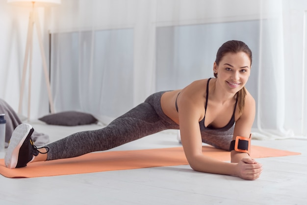 Mantendo em forma. mulher jovem e atraente, alegre, de cabelos escuros, sorrindo e fazendo exercícios enquanto está sentado no tapete