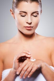 Mantendo sua pele lisa e fresca. linda mulher madura envolta em toalha, espalhando creme na mão, em pé contra um fundo cinza