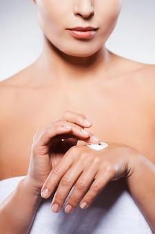 Mantendo suas mãos jovens e frescas. imagem recortada de uma mulher madura enrolada em uma toalha, espalhando creme na mão, em pé contra um fundo cinza