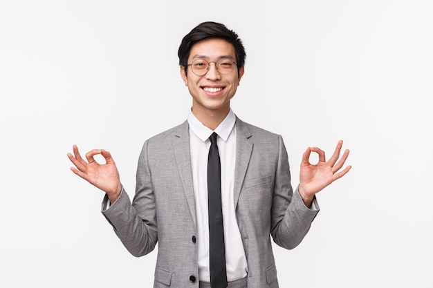Mantenha a calma e mantenha-se saudável. alegre alegre sorridente empresário masculino asiático, trabalhador de escritório, ficar calmo, de mãos dadas em gesto zen, relaxante, meditando, em uma parede branca