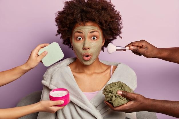Mantenha sua beleza. mulher atordoada e emocional olhando para a câmera, recebendo tratamento de beleza em casa