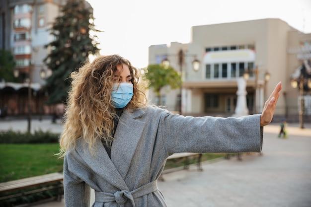 Mantenha sua distância social. mulher com máscara facial de proteção contra vírus, mostrando o gesto de parar a infecção. pandemia de coronavirus covid-19 e conceito de saúde.