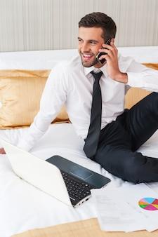 Manter contato com os colegas. jovem alegre de camisa e gravata, trabalhando no laptop e falando ao telefone celular enquanto está sentado na cama no quarto do hotel