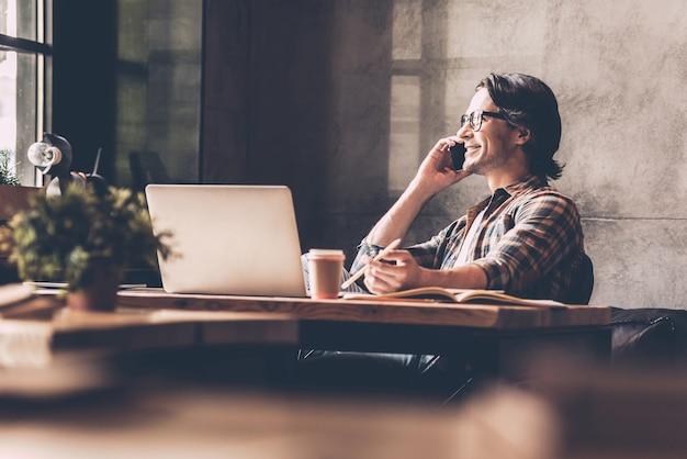 Manter contato com seus colegas. jovem alegre em roupas casuais, olhando pela janela e falando ao telefone celular, enquanto está sentado perto da mesa no escritório criativo