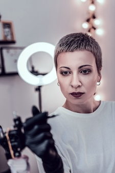 Manter equipamentos especiais. mestre feminino com cabelo curto e olhos grandes observando detalhes de sua máquina