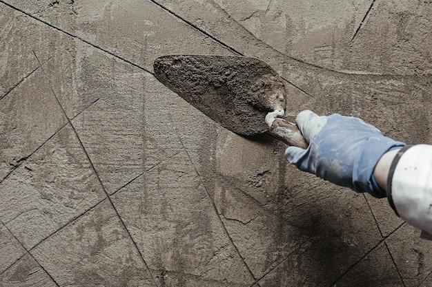 Manual de trabalho do trabalhador com ferramentas de reboco de parede dentro de uma casa