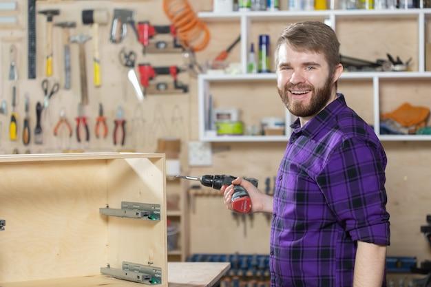 Manufatura, pequenas empresas e conceito de trabalhador - homem trabalhando na fábrica de móveis.