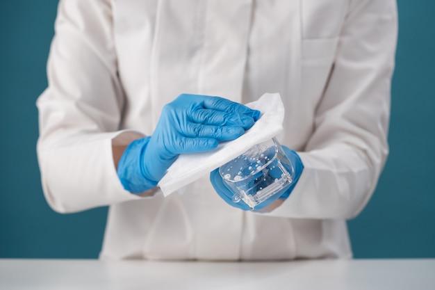 Manuseio e limpeza com luvas azuis com um pano por um profissional de saúde de óculos de segurança após contato com um paciente com doença viral