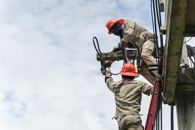 Manutenção de eletricistas trabalhando em alta tensão na caçamba