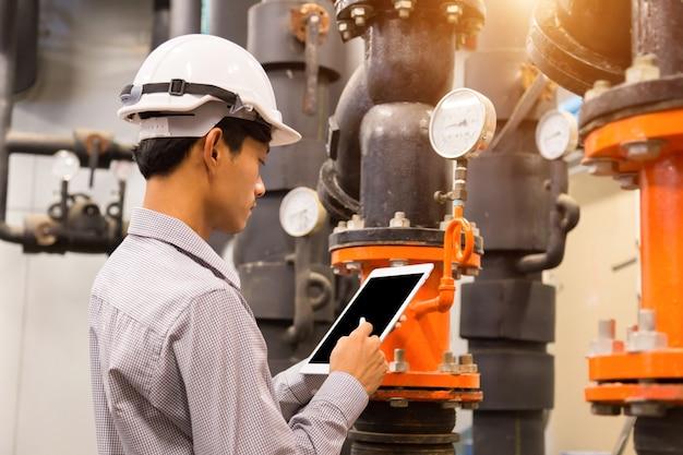 Manutenção de engenheiro asiáticos, verificação de dados técnicos do sistema de equipamentos bomba de água do condensador e manômetro