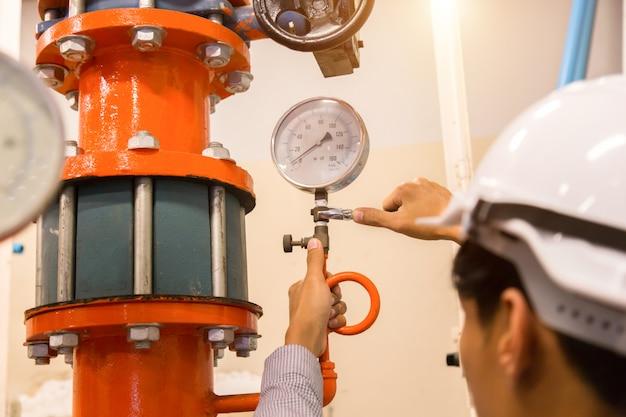 Manutenção do engenheiro asiático verificando dados técnicos do equipamento do sistema condensador bomba de água e manômetro, bomba de água do chiller com manômetro.