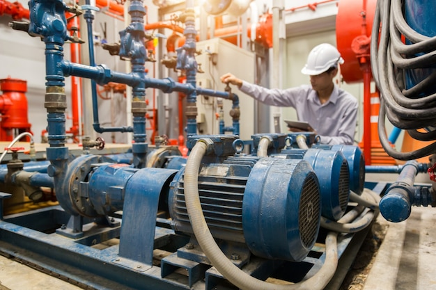 Manutenção do engenheiro asiático verificando dados técnicos do equipamento do sistema condensador bomba de água e manômetro, bomba de água.