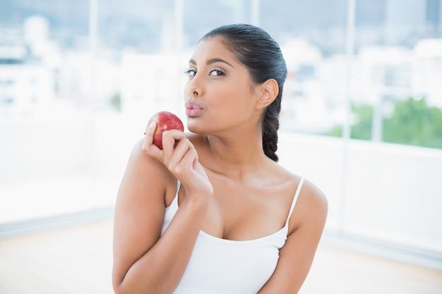 Manzana segurando morena calma e tonificada