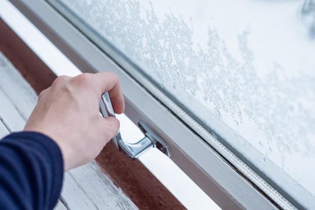 Mão abrindo a janela de bloqueio com flocos de gelo no inverno