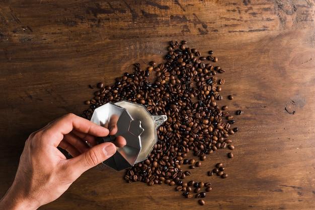 Mão abrindo a tampa da cafeteira perto de grãos de café