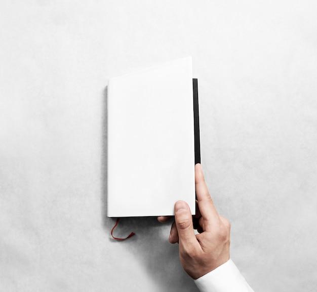 Mão abrindo modelo de maquete de capa de livro branco em branco