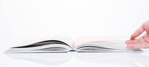 Mão abrindo o livro sobre fundo branco