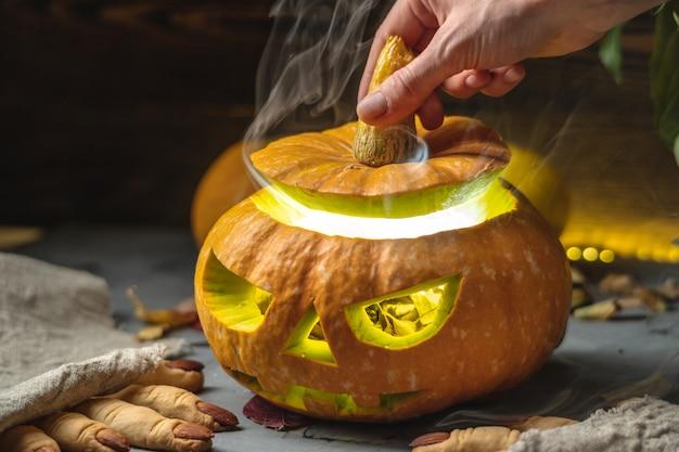 Mão abrindo uma abóbora com um rosto recortado para o halloween, com fumaça saindo dela