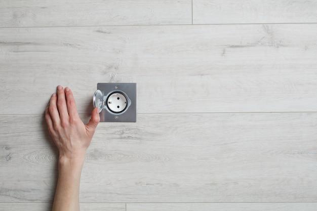Mão abrir um soquete de prata em uma parede bege com espaço de cópia de texto
