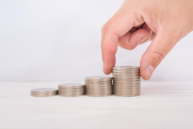 Mão adiciona moeda à pilha de moedas, economizando o conceito de dinheiro