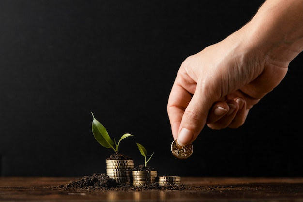 Mão adicionando moedas para empilhar coberto de sujeira e plantas