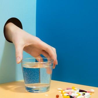 Mão agarrando o copo de água com comprimidos ao lado