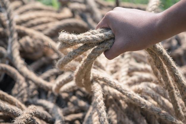Mão agarrando o rolo de corda.