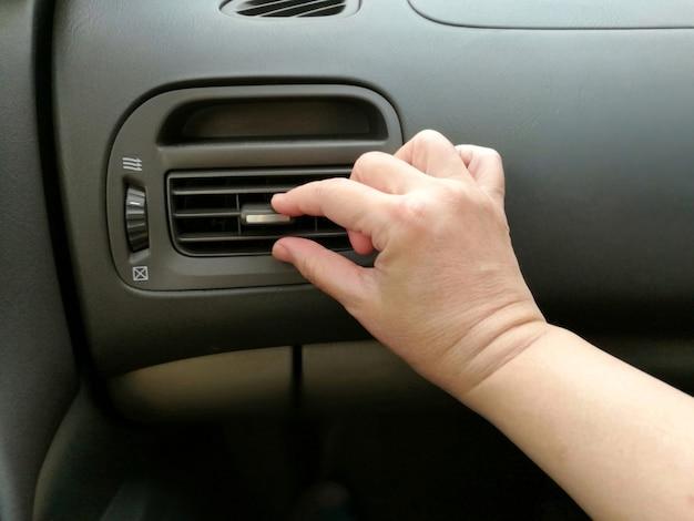 Mão ajustando aberturas de ar do carro
