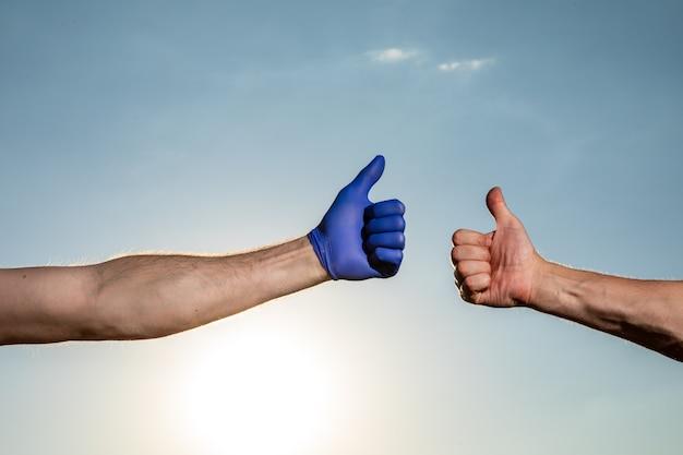 Mão amiga. duas mãos estendendo-se uma para a outra contra o céu azul nublado.